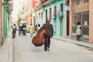 In this picture a man is carrying his bass down a Cuban street lined with colorful buildings.
